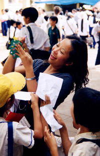 """After giving out scholarships, we went to the school courtyard to interact with the other students, giving them school supplies and Christmas cards. Here, Jasmine from Vancouver signs her name for the kids."""
